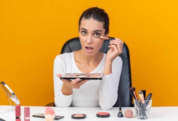 Donna abbastanza caucasica sorpresa che si siede al tavolo con gli strumenti di trucco che tengono la tavolozza dell'ombretto e che applica l'ombretto isolato sulla parete arancione con lo spazio della copia