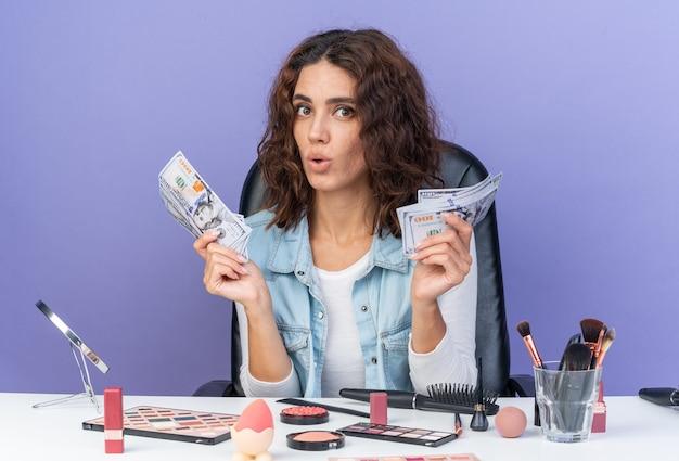 Donna abbastanza caucasica sorpresa che si siede alla tavola con gli strumenti di trucco che tengono soldi