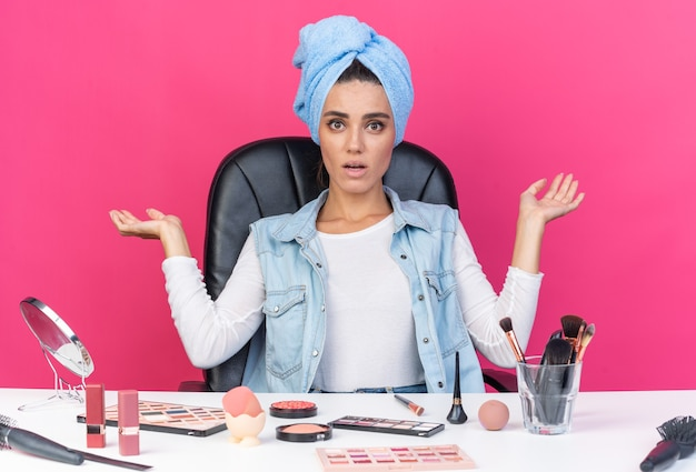 Удивленная симпатичная кавказская женщина с обернутыми волосами в полотенце сидит за столом с инструментами для макияжа, держа руки открытыми