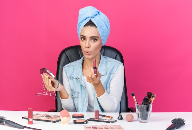 Surprised pretty caucasian woman with wrapped hair in towel sitting at table with makeup tools holding mirror and lipstick
