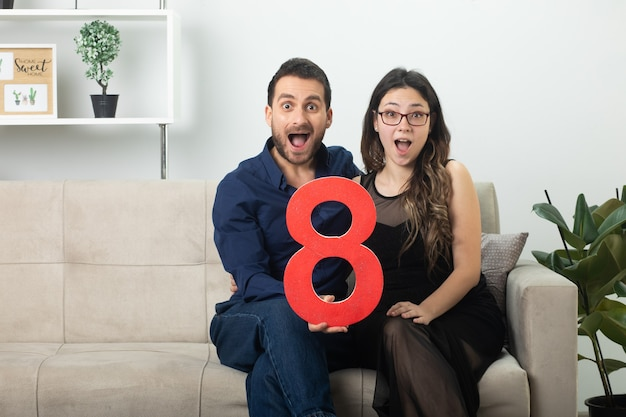 Surprised pretty couple holding red eight figure sitting on couch in living room on march international women's day