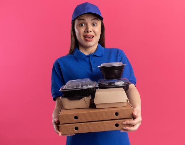 제복을 입은 놀란 예쁜 배달 여자는 피자 상자에 식품 패키지와 용기를 보유하고 분홍색에 카메라를 쳐다 본다.