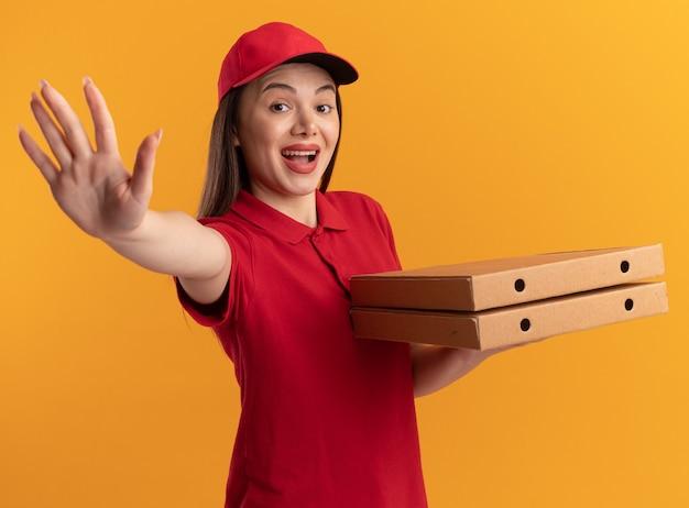 Sorpresa bella donna delle consegne in uniforme fa cinque gesti e tiene in mano scatole per pizza