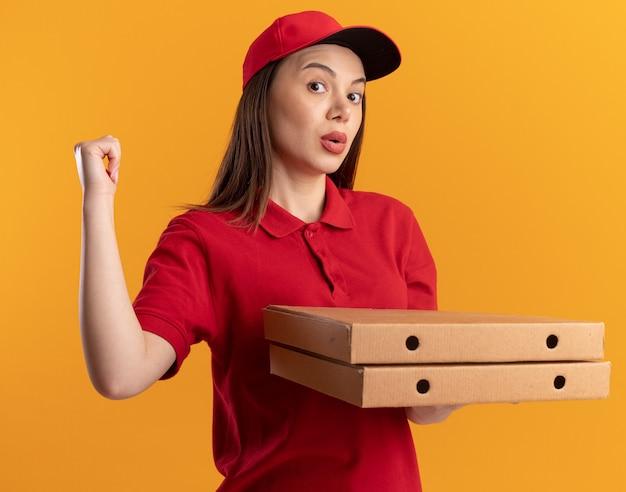 La graziosa donna delle consegne sorpresa in uniforme tiene le scatole della pizza e punta indietro