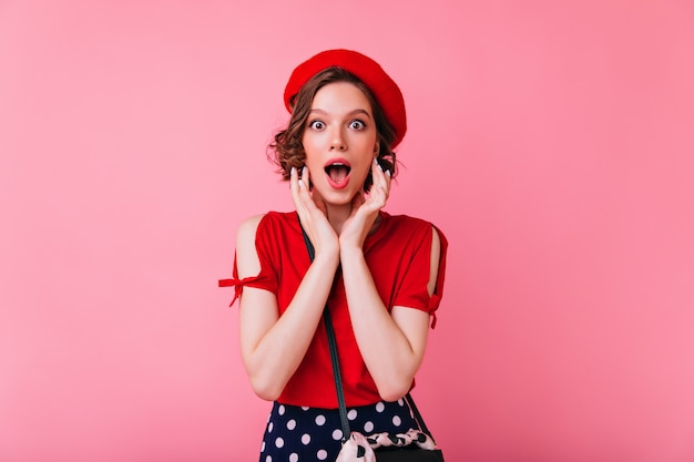 Surprised pretty girl in french beret posing with mouth open. caucasian lady in elegant red blouse standing.