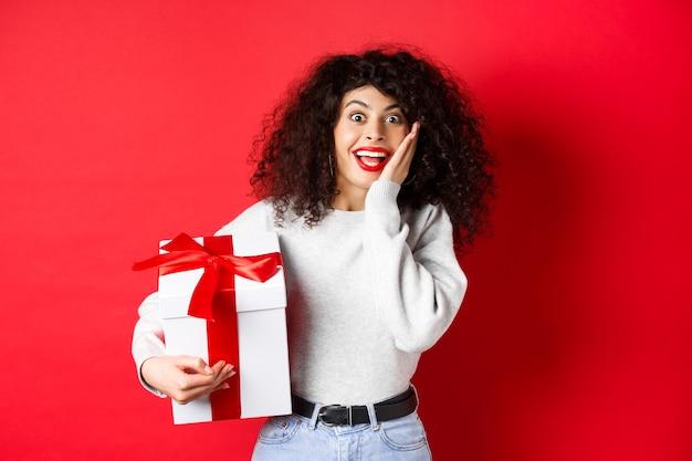 놀란 된 예쁜 여자는 발렌타인 데이 로맨틱 선물, 선물 상자를 들고 빨간색 배경에 서 카메라에 불신과 행복을 찾고 있습니다.