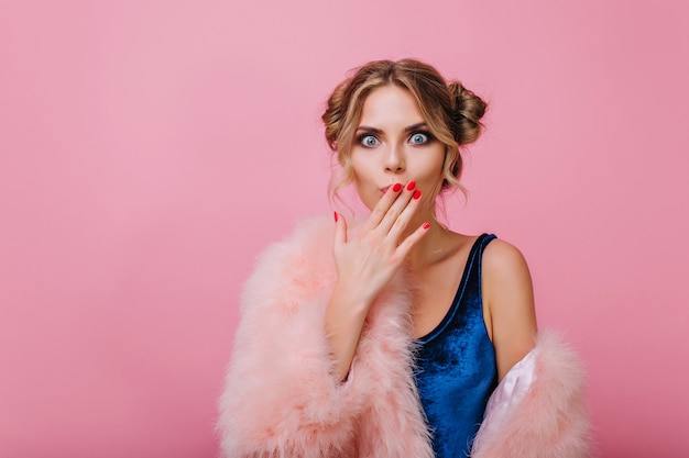 Surprised pretty girl with cute hairstyle said something wrong, while posing in front of pink wall. adorable young woman in velvet bodysuit cover her mouth with hand, isolated on bright background