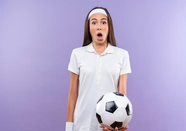 Ragazza abbastanza sportiva sorpresa che indossa la fascia e il braccialetto che tengono il pallone da calcio isolato sullo spazio viola