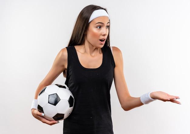 Ragazza abbastanza sportiva sorpresa che indossa la fascia e il wristband che tengono il pallone da calcio che esamina il lato e che mostra la mano vuota isolata su spazio bianco