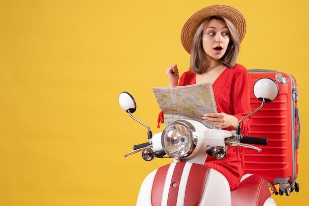 Удивленная красивая женщина в панамской шляпе на мопеде с красным чемоданом держит карту