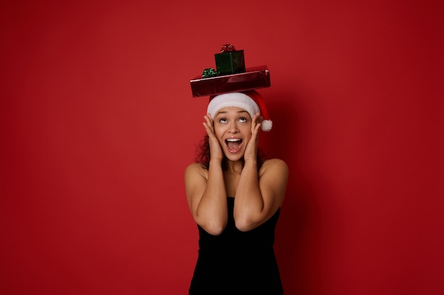 산타 모자와 이브닝 블랙 드레스를 입은 놀란 예쁜 여성이 머리에 있는 크리스마스 선물 상자를 올려다보며 기뻐하며 뺨에 손을 얹고 행복을 표현하고 빨간색 배경에 격리되어 있습니다.