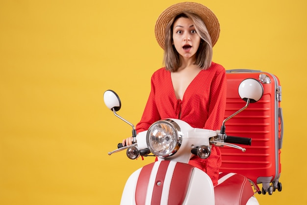 Surprised pretty woman on moped with red suitcase