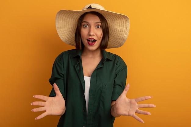 ビーチ帽子をかぶった驚いたきれいな女性は、オレンジ色の壁に隔離された手を開いて保持します。
