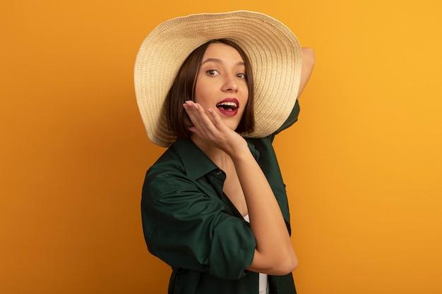 ビーチ帽子をかぶった驚いたきれいな女性は、あごに手を置き、オレンジ色の壁に隔離された正面を見て
