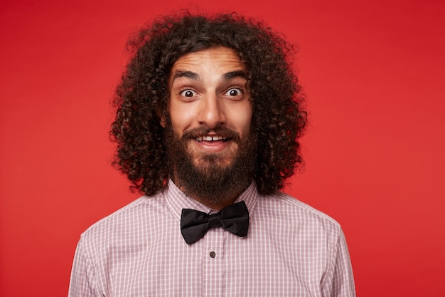 Surprised pretty young brunette male with beard rounding his brown eyes while looking to camera, raising eyebrows amazedly and wrinkling forehead while posing against red background