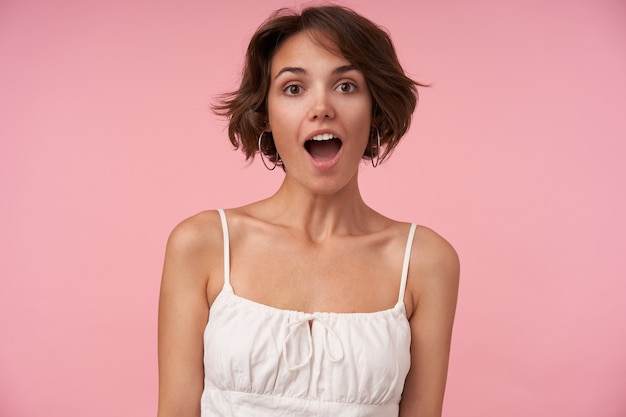 Surprised pretty young brunette woman with short haircut looking with wide eyes and mouth opened, posing with hands down