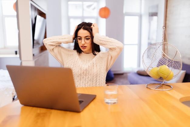 Sorpresa la giovane donna graziosa sta sedendosi sulla cucina e sta lavorando al suo computer portatile e telefono cellulare