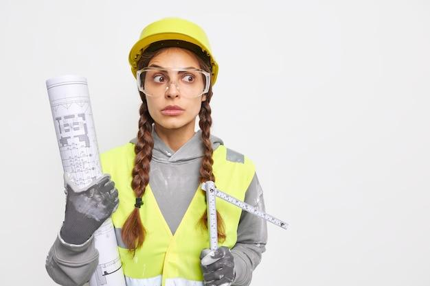 驚いたプロの女性エンジニア開発者は青写真を持ち、巻尺は作業や修理の準備ができた安全服を着て、空白の白い壁の上に建設アシスタントを隔離する