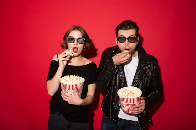Surprised punk couple eating popcorn and looking