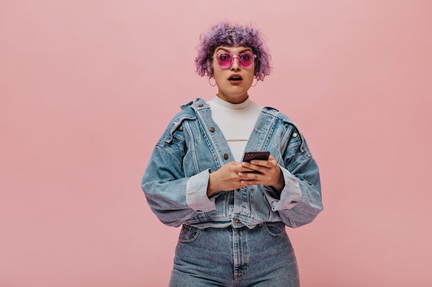 Donna dai capelli viola sorpresa in occhiali rosa e abito di jeans. la donna con i grandi orecchini rotondi tiene il telefono.