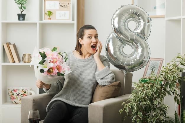 행복한 여성의 날 거실에 안락의자에 앉아 꽃다발을 들고 있는 아름다운 소녀의 뺨에 손을 대고 놀람
