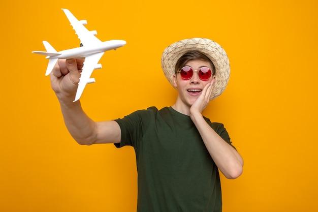 주황색 벽에 격리된 장난감 비행기를 들고 안경을 쓰고 모자를 쓴 젊고 잘생긴 남자가 뺨에 손을 대고 놀란다