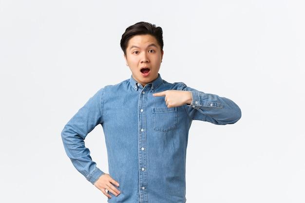Bel ragazzo asiatico sorpreso e interrogato in camicia blu, indicando se stesso con una faccia curiosa, menzionato o nominato, scelto dalla folla, in piedi sfondo bianco