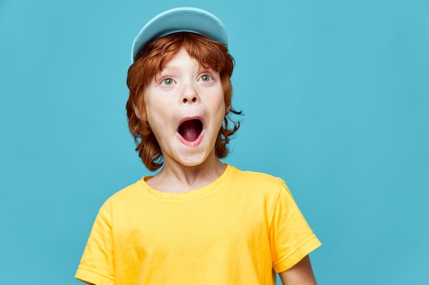 Surprised red-haired boy with open mouth looking up yellow t-shirt cap on his head blue background