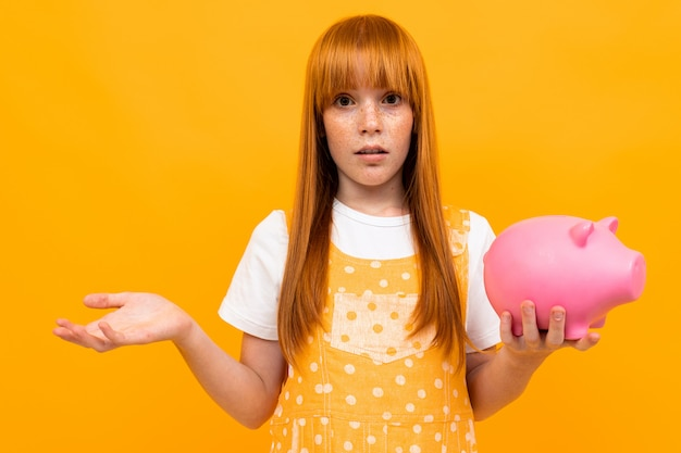 Surprised red-haired girl holds an empty piggy bank on a yellow