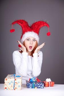 ギフトボックス付きのクリスマスキャップで驚いた赤毛の女の子。