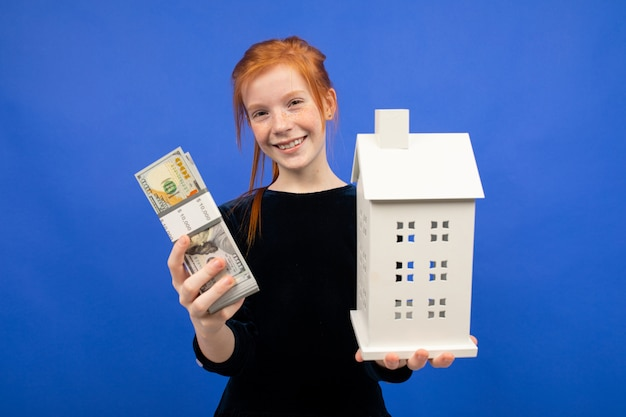 Surprised red-haired girl received money on a blue. lottery housing gain