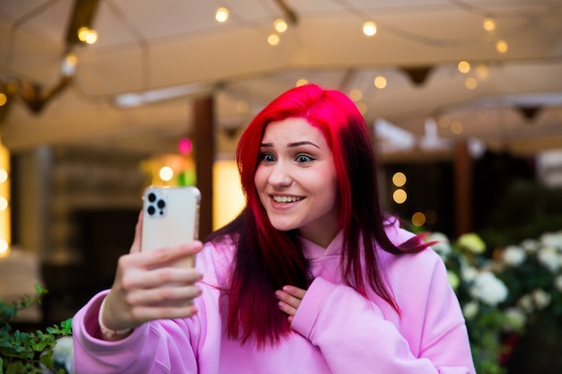 놀란 빨간 머리 인플루언서 블로거 소녀는 소셜 네트워크에서 구독자와 스마트폰을 사용하여 화상 통화를 하고 있습니다.