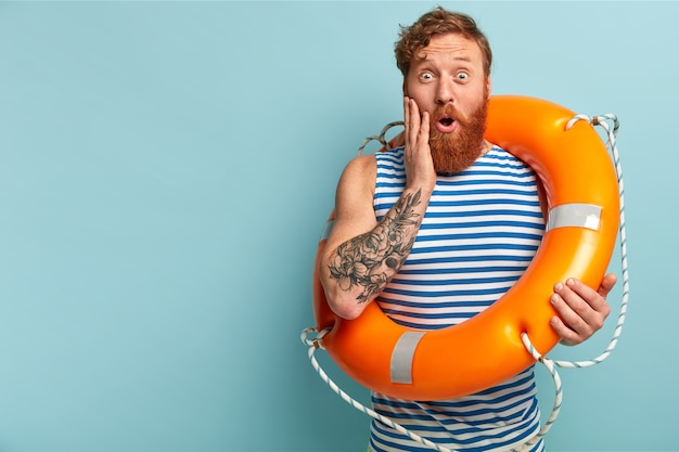 Surprised red haired lifeguard amazed by some hazards on water, carries life buoy, prevents drownings