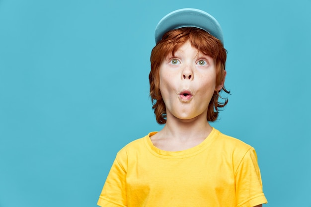 Surprised redhead boy with open mouth looking up blue cap yellow t-shirt cropped view