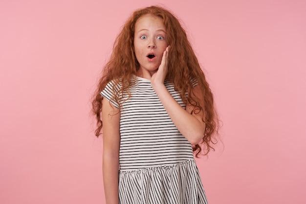 ピンクの背景の上にポーズをとって、縞模様のドレスを着て、彼女の頬に手のひらを保ち、広い目と口を開いてカメラを驚かせて見ているカジュアルな髪型の驚いた赤毛の巻き毛の女性の子供