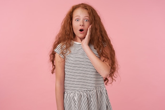 Surprised redhead curly female kid with casual hairstyle posing over pink background, wearing striped dress, keeping palm on her cheek and looking amazedly to camera with wide eyes and mouth opened