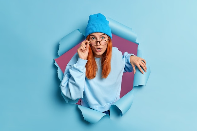 Surprised redhead european woman has shocked face expression stares with eyes popped out reacts on astounding news wears casual jumper and hat.