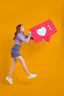 놀란 빨간 머리 여성이 좋아하는 것을 쫓고 소셜 미디어 심장 아이콘을 유지하는 점프하는 여성을 감사합니다.