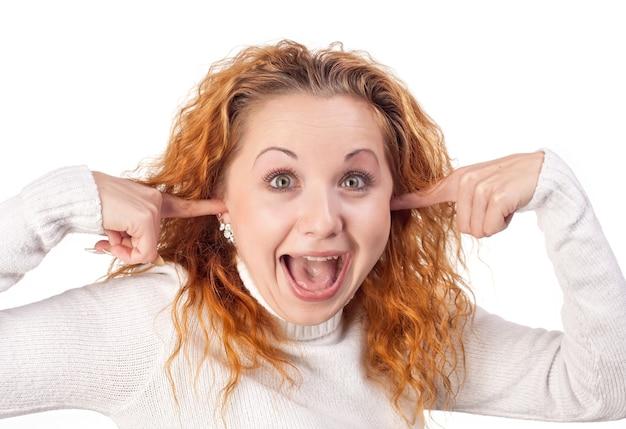 놀란 된 빨강 머리 소녀 손으로 그녀의 귀를 닫습니다.