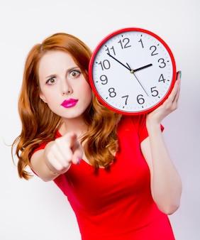 Удивленная рыжая девушка в красном платье с большими часами на белом