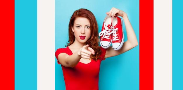 파란색에 덧 신과 빨간 드레스에 놀란 된 빨간 머리 소녀.