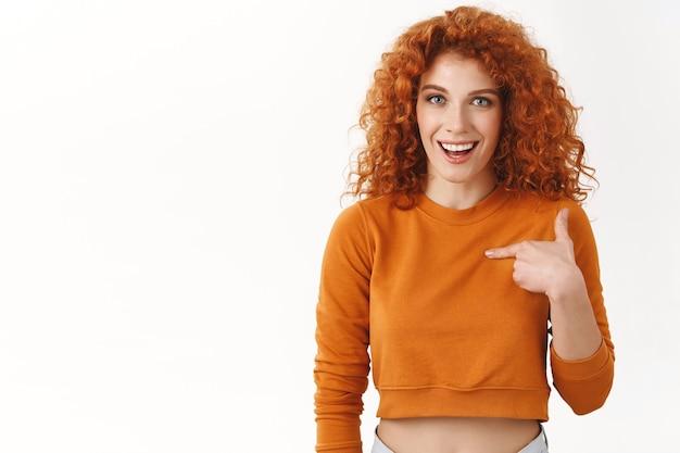 Ragazza rossa sorpresa che indica se stessa chiedendosi se è vincitrice, sorridendo allegramente sorpreso notizie piacevoli, ricevendo un invito festa fresca, sembra impressionato e meravigliato, stando in piedi sul muro bianco