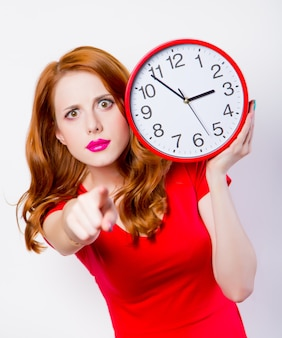 Surprised redhead girl in red dress with big clock on white