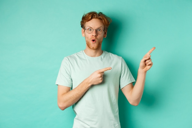 Surprised redhead guy in glasses and t-shirt checking out special deal, pointing at upper right corner promo and gasping in awe, showing banner, standing over turquoise background.