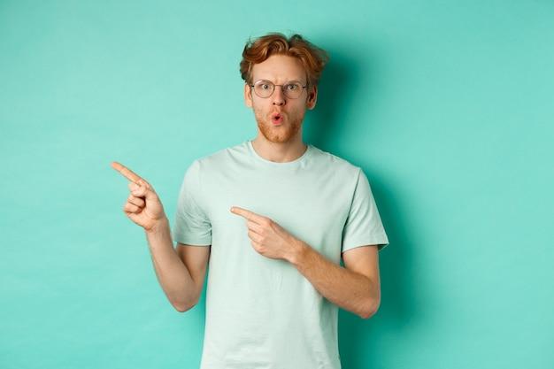 Удивленный рыжий парень в очках и футболке показывает пальцем влево, говорит «вау» и показывает промо-предложение, проверяет специальное предложение, стоя на бирюзовом фоне.