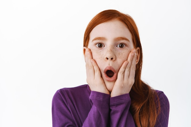 Surprised redhead little girl with freckles gasping, saying wow and looking amazed impressed at front, standing over white wall