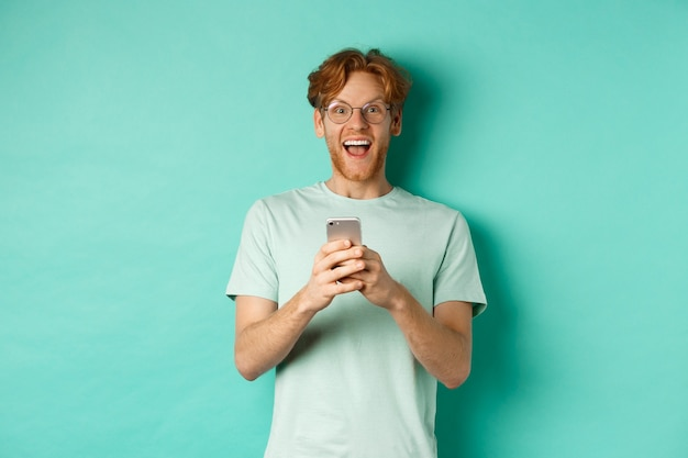 청록색 배경에 서있는 스마트 폰 프로모션 제안을 읽은 후 카메라에 놀란 안경에 놀란 빨간 머리 남자.