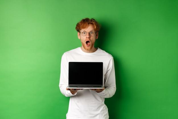 노트북 빈 화면을 보여주는 안경에 놀란 된 빨간 머리 남자, 온라인 프로 모션 및 드롭 턱을 보여주는, 카메라를 쳐다보고 놀 랐 다, 녹색 배경.