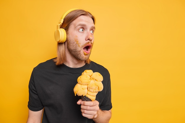 Surprised redhead man looks away shocked keeps mouth opened eats delicious ice cream being stunned by something wears stereo headphones black t shirt isolated over yellow wall copy space