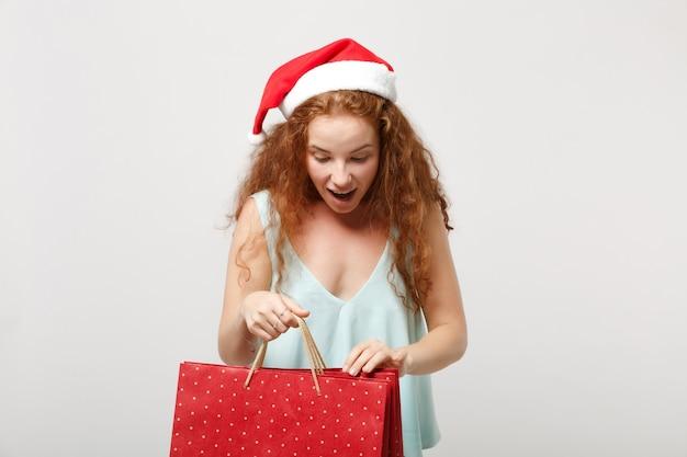 Удивленная рыжая девушка санты в шляпе рождества изолированной на белой предпосылке. с новым годом 2020 праздник праздник концепции. копируйте пространство для копирования. держите пакет с подарком или покупками после покупок.
